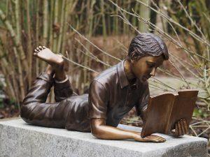 Tuinbeeld - bronzen beeld - Liggende lezende Jongen - 35 cm hoog