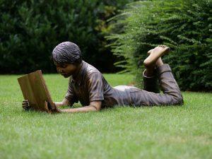Tuinbeeld - bronzen beeld - Liggende lezende jongen - 46 cm hoog